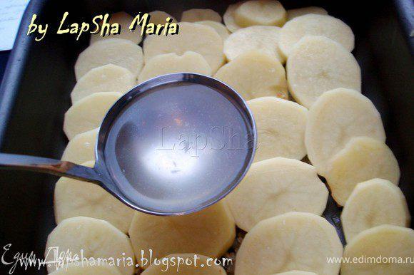 Картофель вымоем, почистим и нарежем на ломтики толщиной примерно 6-7 мм. Выложим слой картофеля внахлест на слой лука. Добавим бульон, так чтобы он покрывал примерно 3/4 картофеля.