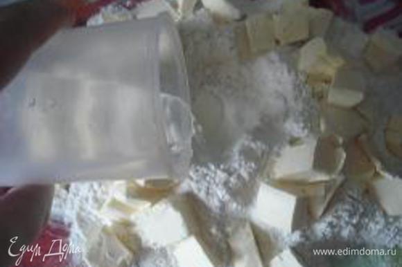 Приготовление теста: Муку просеять с разрыхлителем, выложить горкой на разделочную доску. Сделать углубление. В углубление налить холодную воду и добавить щепотку соли. Масло нарезать мелкими кусочками и выложить по кругу.