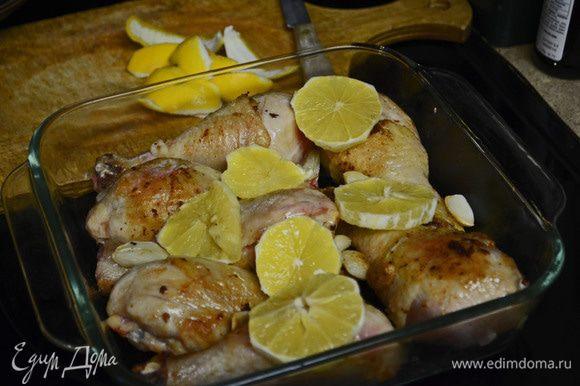 В большой сковороде разогреть сливочное и оливковое масло. Обжарить окорочка со всех сторон до золотистого цвета. В конце процесса добавить целые зубчики чеснока и немного их обжарить. Обжаренные окорочка положить в огнеупорную посуду, равномерно разложить чеснок и кружки лимона.