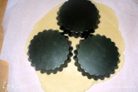 Через час достать тесто.Его лучше раскатывать между двумя листами пергамента. При формочках диаметром 12 см получается 6 корзиночек. Я всегда покрываю дно формочек пергаментом. Бортики формочек смазать сливочным маслом.