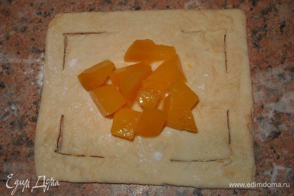 Размораживаем тесто, разрезаем на небольшие квадратики 10*10см. делаем надрезы. На центр выкладываем начинку, посыпаем корицей.