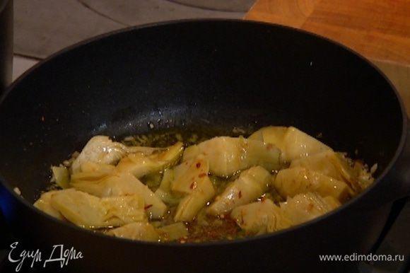 Сухой перец раскрошить и посыпать лук с артишоками.