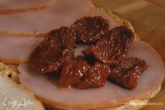 Нижний пласт смазать горчицей, сверху разложить ветчину и вяленые помидоры.