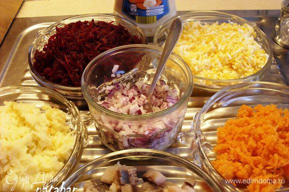 Филе сельди обмыть и обсушить. Лук почистить. Сельдь и лук мелко нарезать на кубики размером 0.5х0.5х0.5 см. Яйца отварить, охладить, почистить и натереть на мелкой тёрке. Картофель, морковь и свёклу почистить, помыть и спецконтейнере для СВЧ сварить в микроволновке. Остудить и натереть на мелкой терке.