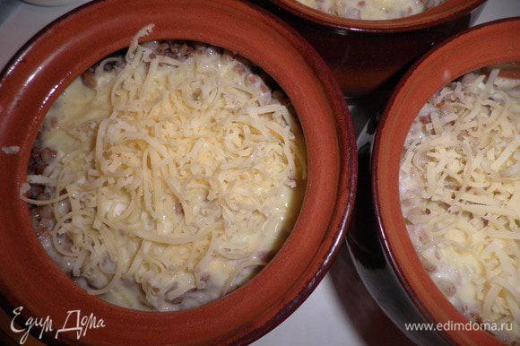 Кашу делим на две части и раскладываем по ровну в горшочки. На кашу выкладываем слой грибов и накрываем оставшейся кашей.Яйца взбить со сметаной и разлить по горшочкам.Сверху посыпать натёртым сыром и запечь в духовке,пока сыр не подрумянится.