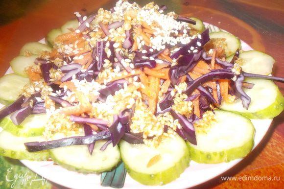 Колечки огурца укладываем на тарелку,сверху кладем капусту и морковь.Поливаем заправкой,посыпаем кунжутом.Подаем.