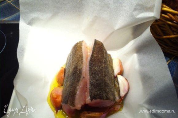 поместить туда рыбу, полить оливковым маслом, посолить, поперчить, положить рядом мытый но нечищенный лук и чеснок