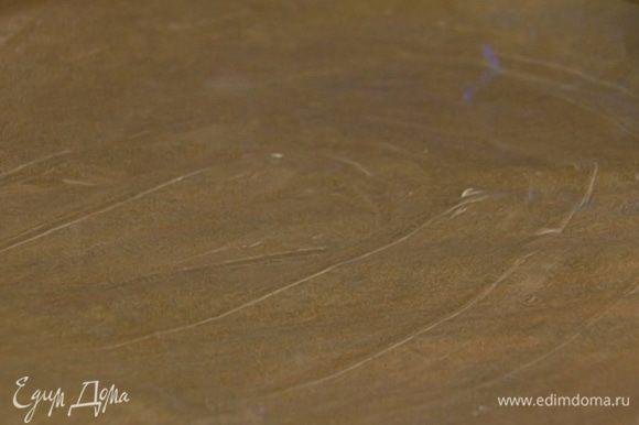 Выстелить противень бумагой для выпечки, смазать ее сливочным маслом.