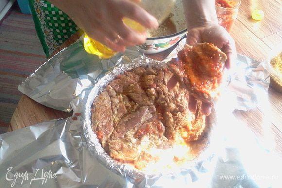 Достаём мясо, обтираем салфеткой, обваливаем в специях. Берём большую чугунную сковароду и застилаем её фольгой. Смазываем фольгу оливковым(подсолнечным маслом). Затем берём ошеек и смазываем его аджикой, укладывая мясо на сковороду аджикой вниз.
