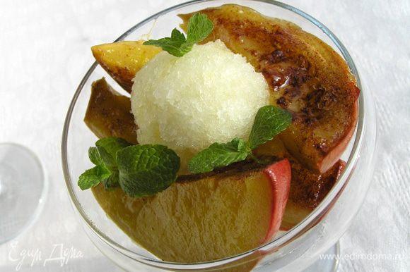 Достать манго из духовки, дать чуть остыть, крупно нарезать. Разложить ломтики по тарелкам или креманкам, присыпать листиками мяты, подавать с шариком мороженого или сорбета.