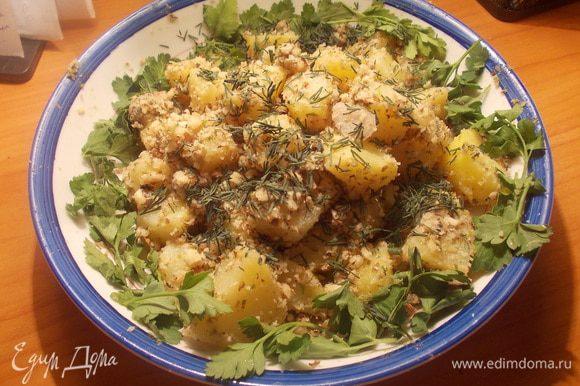 Картофель перемешать с ореховой масой, выложить на блюдо, и украсить петрушкой и укропом.