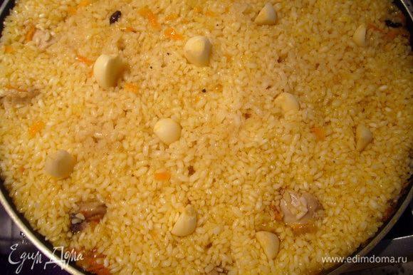 Примерно за 5 минут до выключения огня, когда рис в состоянии аль денте (готовый снаружи и твердоватый внутри) я втыкаю по всей поверхности сковороды очищенные зубчики чеснока. Если бы это был казан на природе, то мы обычно вглубь плова вставляем целую головку чеснока, очищенную только от внешней чешуи. Выравниваем поверхность ложкой (чтобы чеснок был внутри риса), накрываю плов крышкой и выдерживаю ещё примерно 5 минут.