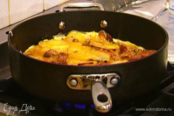 Добавить жареный картофель, все перемешать и выложить обратно на сковороду, равномерно распределить и на медленном огне дать омлету пропечься.