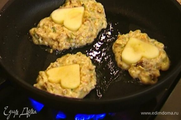 Разогреть в сковороде оливковое масло, ложкой выкладывать в нее тесто в виде лепешек, на каждую лепешку положить по яблочной фигурке и чуть-чуть ее вдавить. Обжаривать оладьи по 3–4 минуты с каждой стороны.