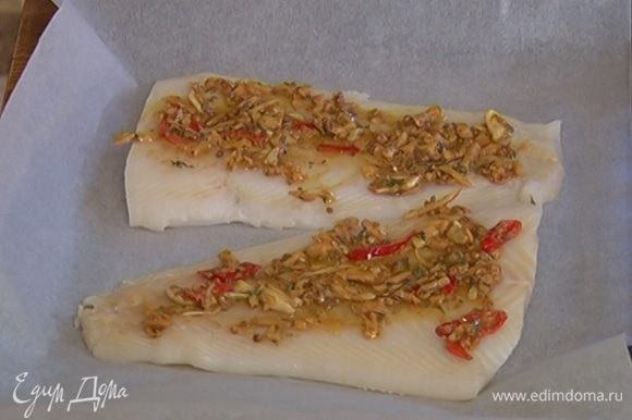 Противень застелить бумагой для выпечки большего размера, в центр выложить рыбу, смазать заправкой, сбрызнуть оливковым маслом.