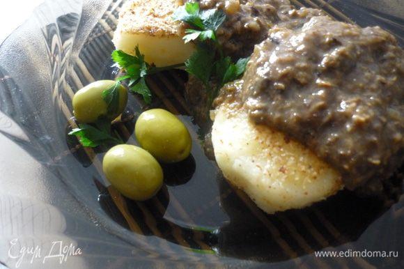 Подавать котлетки, полив грибной икрой и украсив оливками и зеленью.