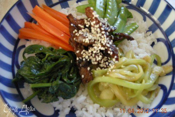 На дно глубокой тарелки выкладываем рис, в центр мясо, по кругу овощи. Поливаем всё кунжутным маслом, соевым соусом. По желанию посыпаем жгучим перцем и кунжутными семечками.