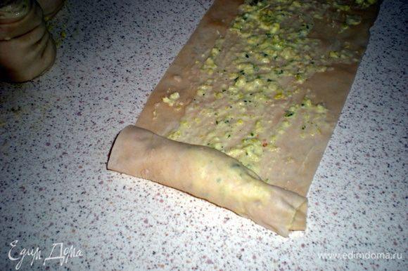 Разрезать тесто на полоски шириной 6-8 см.Смазать каждую луковой смесью.Скатать в рулет.