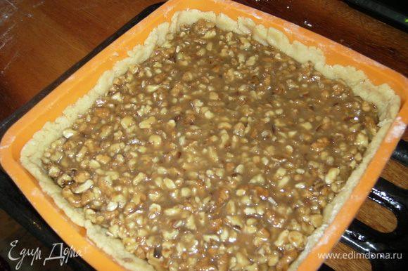 Тесто делим на 2 части (1 часть чуть больше второй). Раскатываем толщиной 3 мм.1 часть кладем в форму на пергамент. Заливаем орехово-карамельную массу.