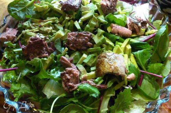 выкладываем салатный микс, добавляем тунец, поливаем готовой заправкой и слегка смешиваем продукты.