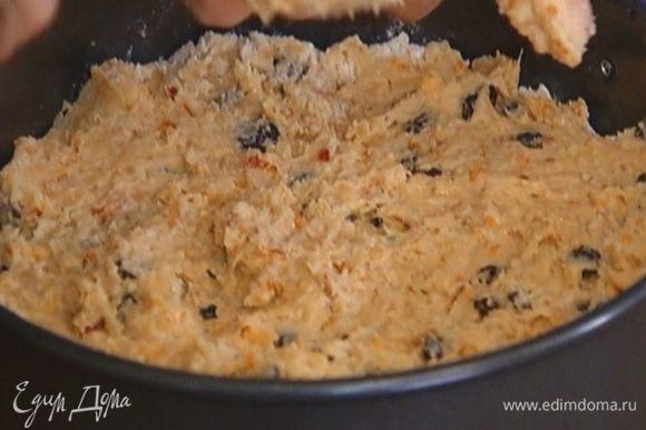 Небольшую разъемную форму смазать оливковым маслом, выложить тесто и разровнять.