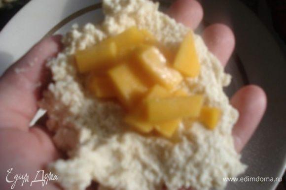 Дать тесту постоять 15 минут. Этого времени достаточно, чтобы набухла манная крупа. В это время 1/2 манго очистить и порезать кубиками. Положить немного теста на ладонь, в центр выложить 1 ч.л. нарезанного манго.