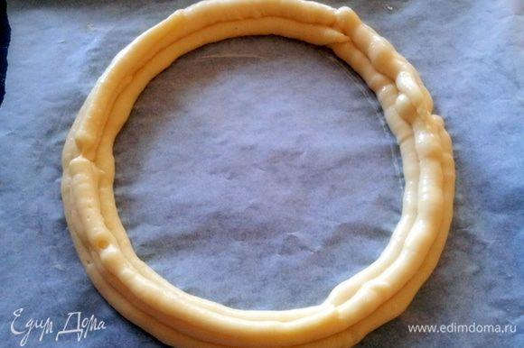 Приготовить противень, застеленный пергаментом и на пергаменте нарисовать круг диаметром 24-26 см. Выдавить из кондитерского мешочка заварное тесто в виде кольца. Затем второе кольцо выдавить внутри первого, А третье разместить между первыми и вторым.