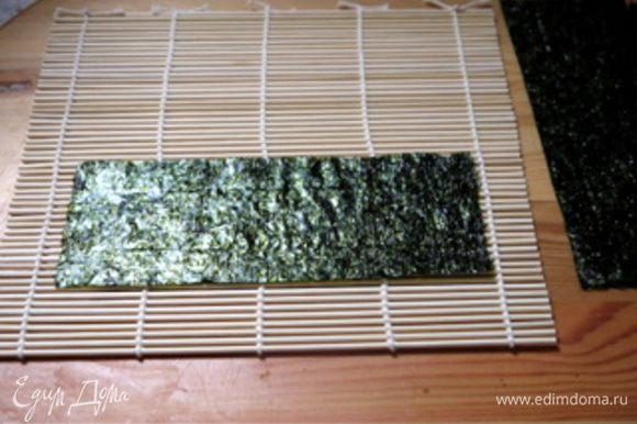 Приготовить циновку для скручивания роллов. Нарезать лист нори на 5 частей для лепестков. Приготовить первый лепесток.