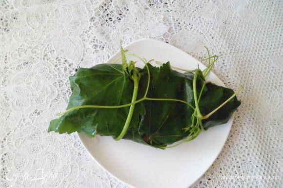 На разделочную доску выложить виноградные листья и завернуть в них готовое филе. Если у Вас нет кулинарной нити, то в качестве нити можно использовать свежую и нежную лозу.