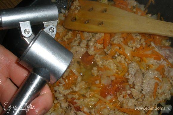 Выложить к фаршу лук с морковью и помидор. Выдавить чеснок. Посолить и поперчить. Все перемешать. Тушить примерно 5 минут без крышки, чтобы вытопилась лишняя влага.