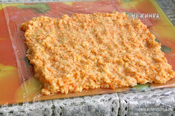 Подготовим рабочую поверхность. На стол или доску кладем пищевую пленку. Немного сбрызгиваем водой. Распределяем «тесто» в виде прямоугольника.