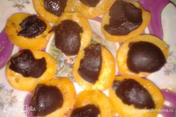 в каждую половинку выложить шоколадный шарик или лепесток,сверху украсить мороженым