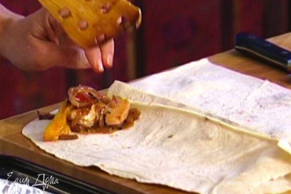 Лаваш разрезать на несколько частей, на каждую выложить индейку с луком, понемногу томатного соуса и сыра и свернуть рулетиками.