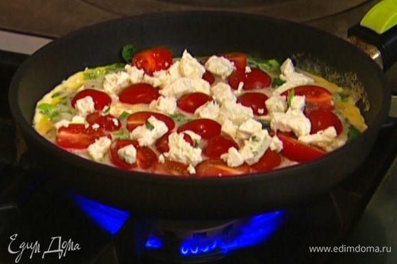 Когда края омлета схватятся, разложить сверху помидоры и кусочки феты, накрыть крышкой и готовить еще 2–3 минуты.