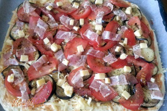 Также тонко нарезать бекон, и положить кубики брынзы. Посыпать все сухим орегано, базиликом и перцем.