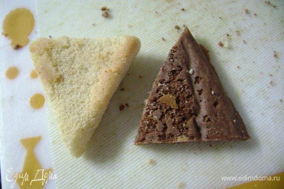 Снять пергаментную бумагу с бисквитов и нарезать прямоугольные бисквиты треугольниками, ориентируясь по форме, со стороной примерно 3 см.