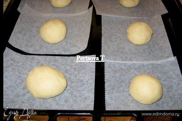 Кладем тесто на рабочий стол и делим на 20 шариков, каждый величиной с грецкий орех. Из пекарской бумаги вырезаем 20 шт. квадратиков. На каждый квадратик кладем по одному шарику, накрываем и оставляем подниматься в течение часа.