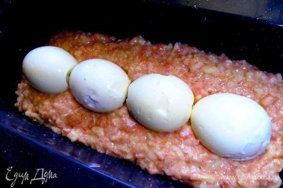 Половину мясной массы выкладываем на дно,а сверху отварные яйца(у меня вошло 4 шт.)
