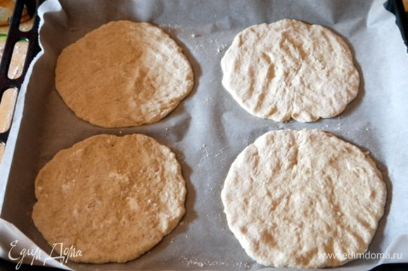 Поднявшееся тесто разделить на 10 одинаковых частей. Раскатать 8 частей в лепёшечки по 1/5 см толщиной (Скалкой пользоваться не обязательно.Тесто хорошо формируется руками). Перенести 4 лепёшки на противень, накрытый бумагой для выпечки.