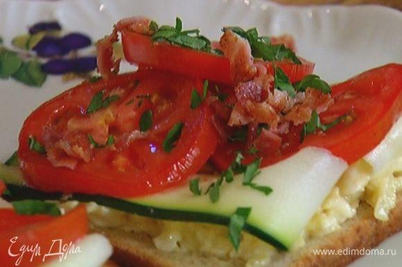 Поджаренный хлеб смазать сырной начинкой, выложить по 2–3 полоски цукини, затем помидоры и бекон, сверху присыпать петрушкой.