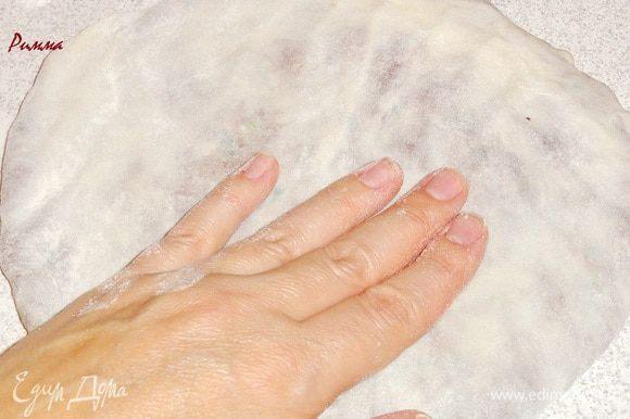 Из получившейся части руками сформуйте круглую (по возможности ) лепешку. Не страшно, если у вас будет рваться тесто, присыпьте это место мукой. Тесто будет почти прозрачным.