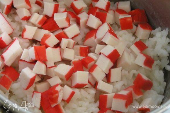 Рис смешайте с нарезанными крабовыми палочками.