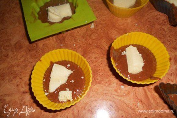 формы на половину наполнить тестом,сверху положить по ломтику белого пористого шоколада
