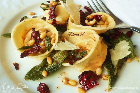 Вынуть тортеллини шумовкой на тарелки (без воды!). Полить маслом с орешками, выложить лепестки пармезана и сразу же подавать.