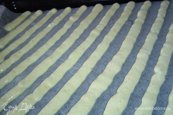Противень застилаем бумагой для выпечки и смазываем маслом. Кондитерский мешок наполняем светлой массой и выдавливаем на противень диагональные полоски с промежутком около 2 см.