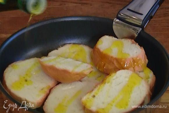 Хлеб нарезать, натереть зубчиком чеснока, выложить в форму для выпечки и слегка сбрызнуть оливковым маслом.