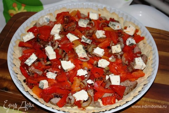 На испеченный корж выкладывам равномерно мясо, потом перцы, томаты и лук. Сыр разломать на небольшие кусочки и выложить сверху. Выпекать пирог при 180 градусах 20 минут.