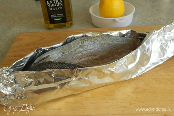 При помощи 2 слоёв фольги зафиксируйте рыбу в вертикальном положении, оставив верхний разрез открытым. Не забудьте предварительно хорошо смазать оливковым маслом внутреннюю сторону фольги и особенно рыбий хвост. Иначе он высохнет.