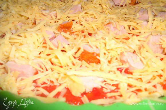 Сверху выложить равномерно порезанную кубиками ветчину и присыпать обильно тертым сыром.