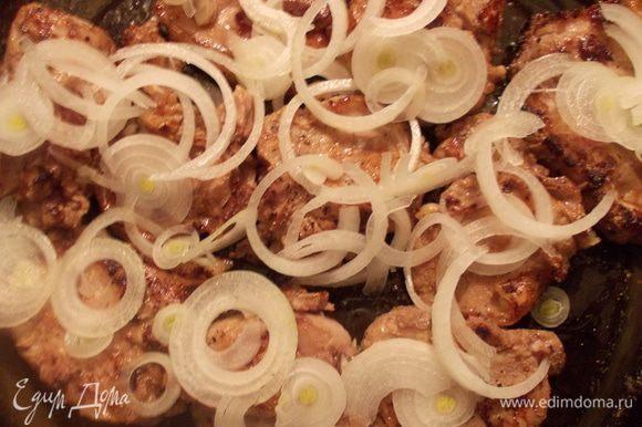 Порезать лук тоненькими кольцами и уложить сверху мяса.
